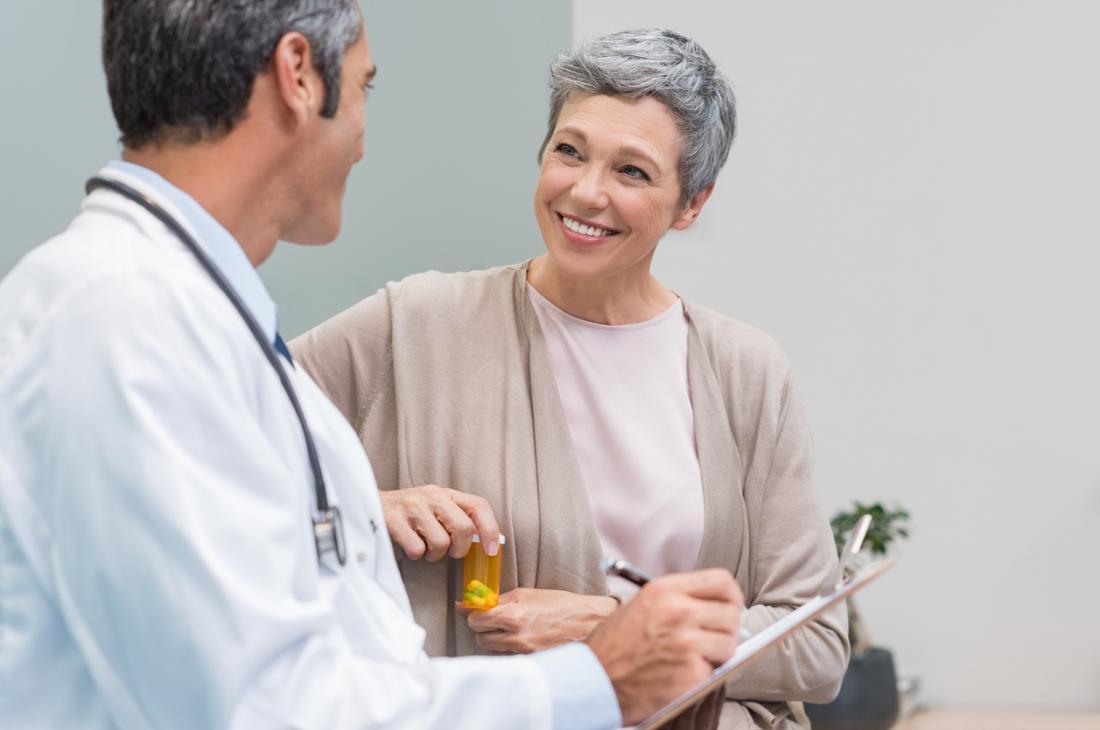 Възрастна жена, говореща с лекар, държаща жълта бутилка с лекарства или хапчета в нея.