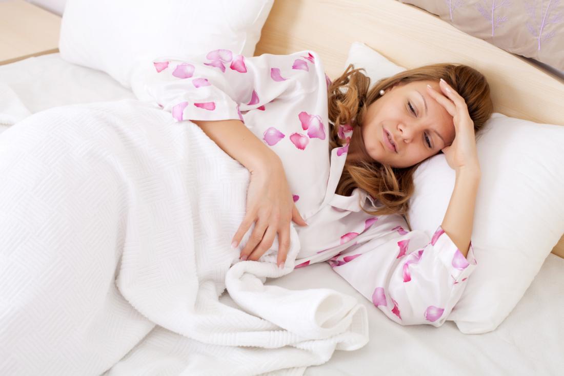 Signora a letto tenendo il suo stomaco
