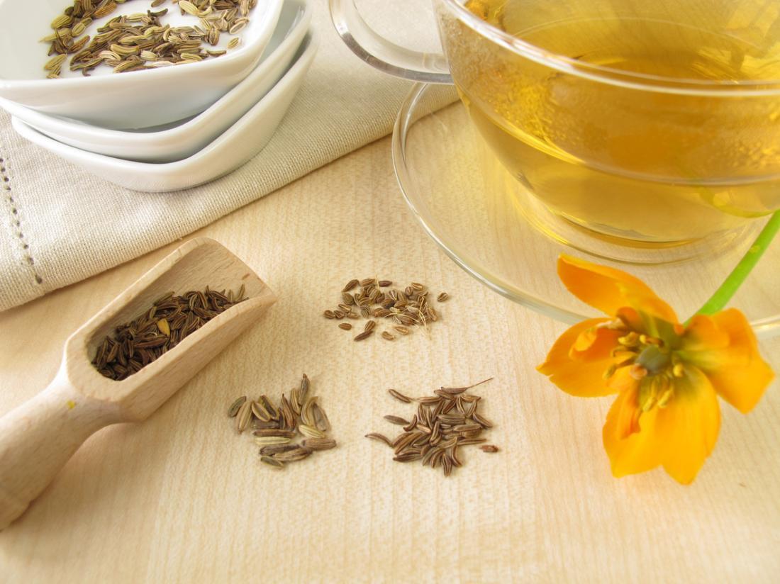 Чай от копър в чиста чаша, с копър семена в купа и дървена лъжица и кимион,