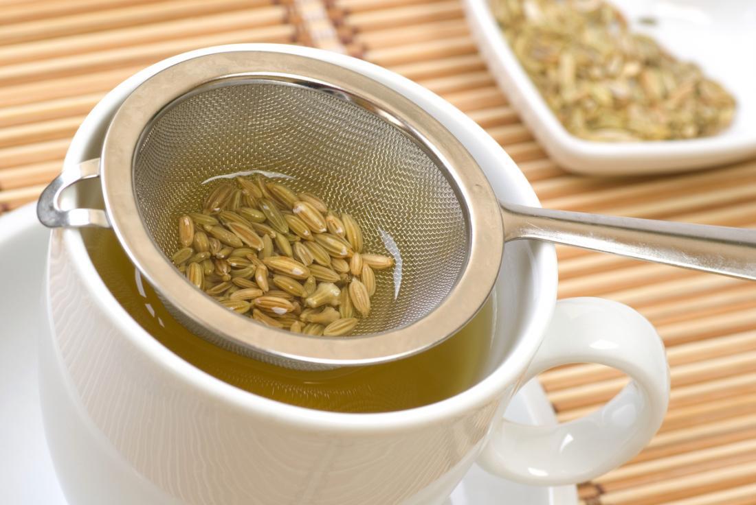 Семена от копър в чай филтър над чаша от билков чай.