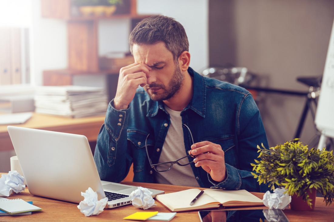 A souligné l'homme au bureau en pinçant le pont de son nez parce qu'il a mal à la tête.