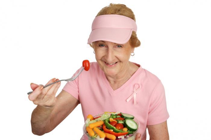 Uma mulher mais velha comendo legumes.