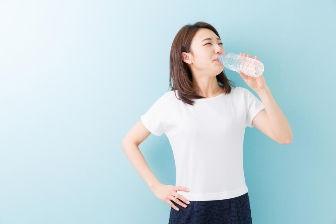 donna che beve molta acqua per un'infezione del tratto urinario