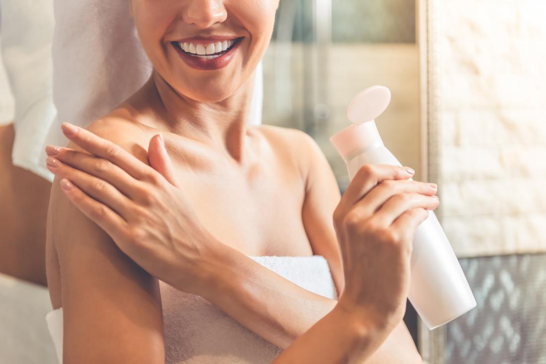 жена овлажнява кожата с лосион