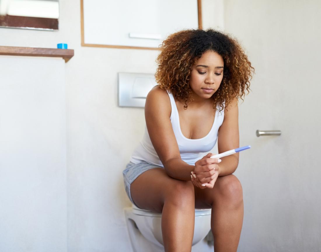 Frau, die auf der Toilette betrachtet Schwangerschaftstest sitzt.