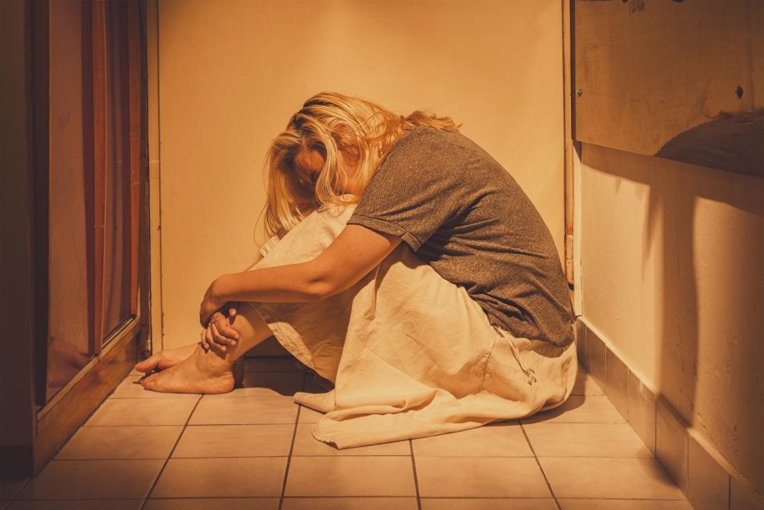 donna accovacciata sul pavimento