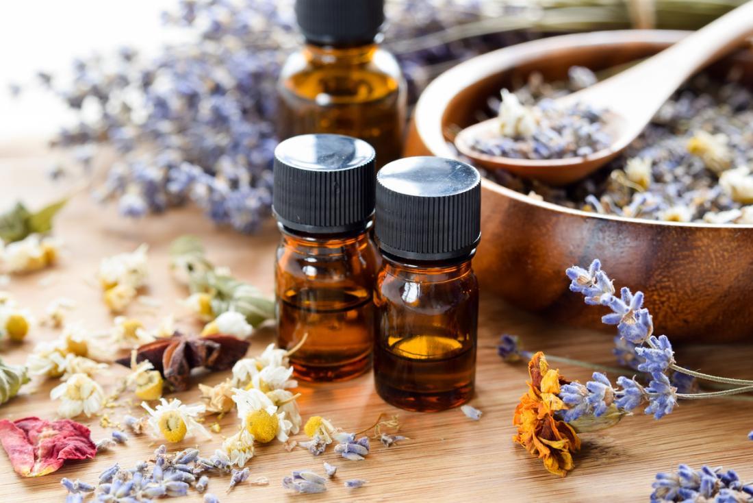 huiles essentielles avec des herbes séchées sur une table