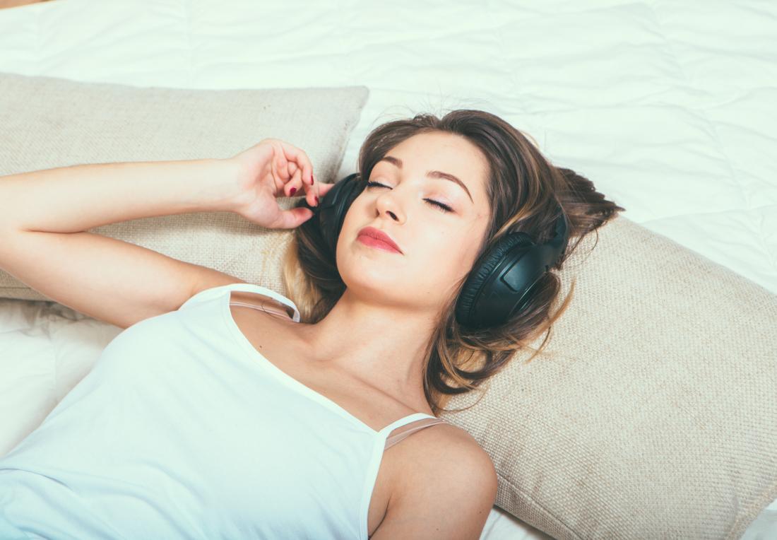 jovem mulher ouvindo música através de fones de ouvido