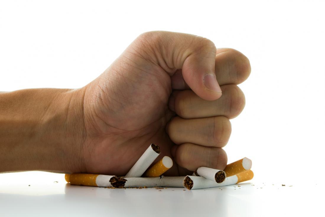 la main de l'homme écrasant des cigarettes