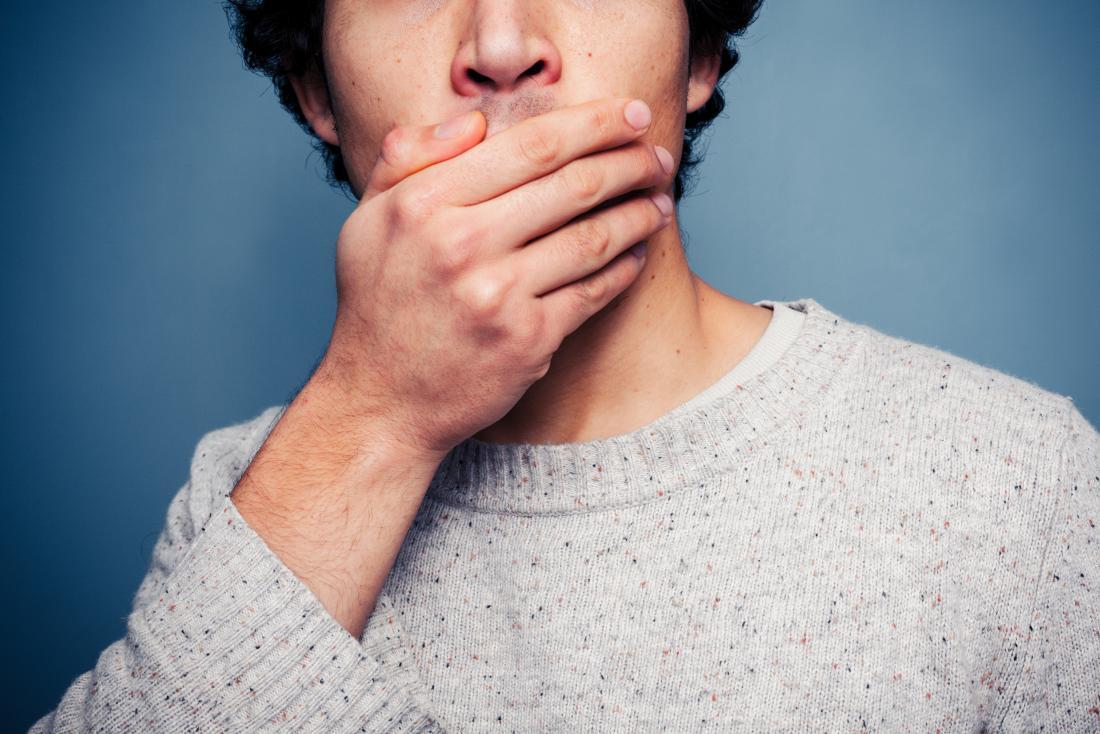 Mężczyzna zakrywa jego usta z jego ręką