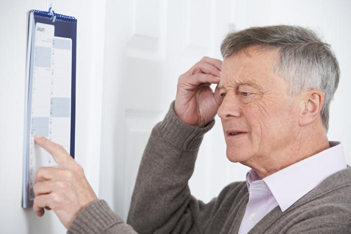 älterer Mann, der einen Kalender verwirrt betrachtet