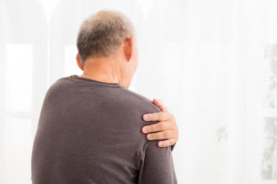 Mann hält seine linke Schulter vor Schmerzen