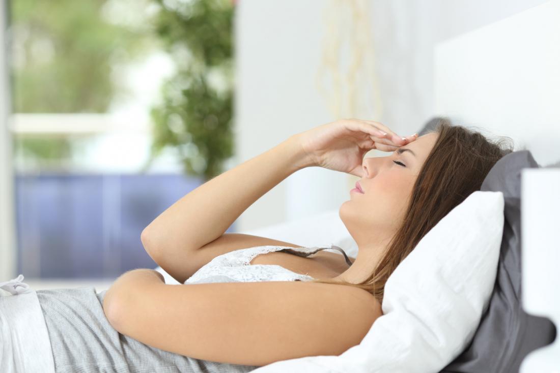 女性は頭痛で横たわっている