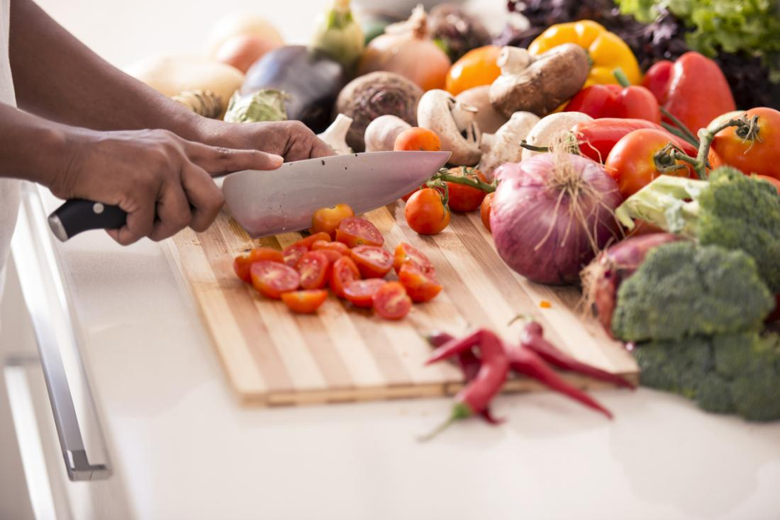 Tomaten werden zerkleinert, umgeben von anderem gesunden Gemüse