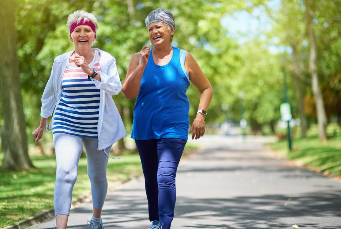 zwei mittleren Alter Frauen Fitness zu Fuß durch den Park