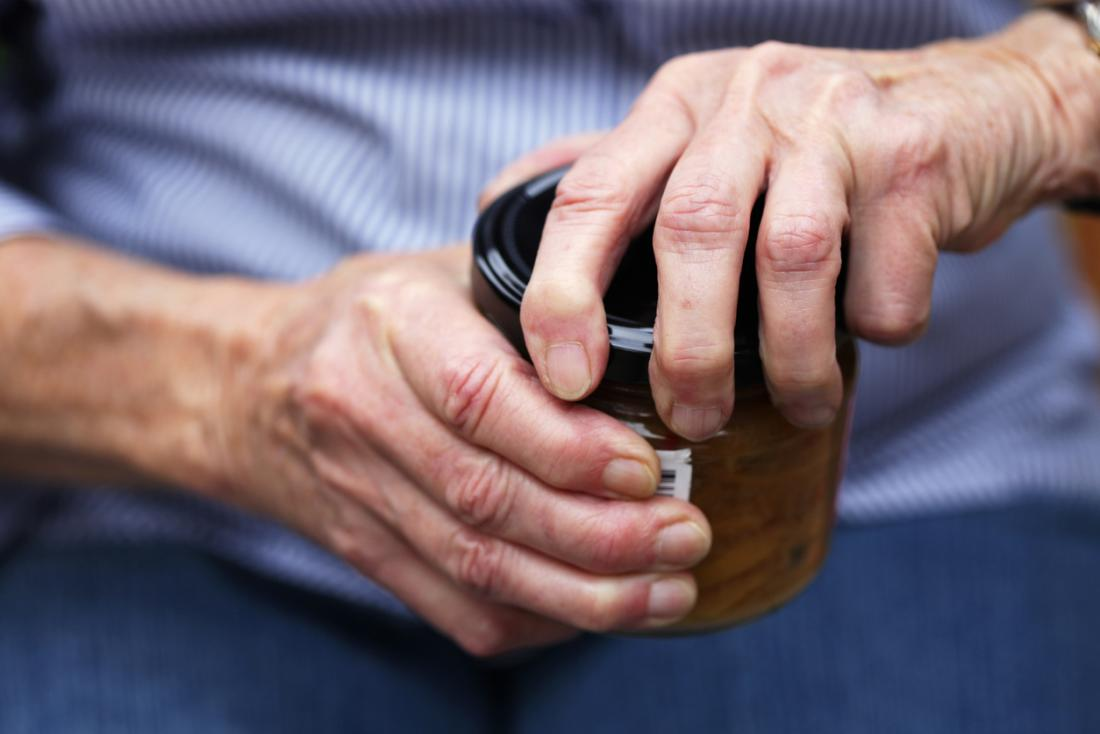 Pessoa idosa com artrite que abre um frasco.