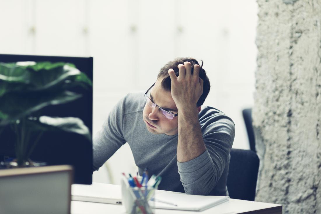 L'homme se sent stressé et anxieux au travail.