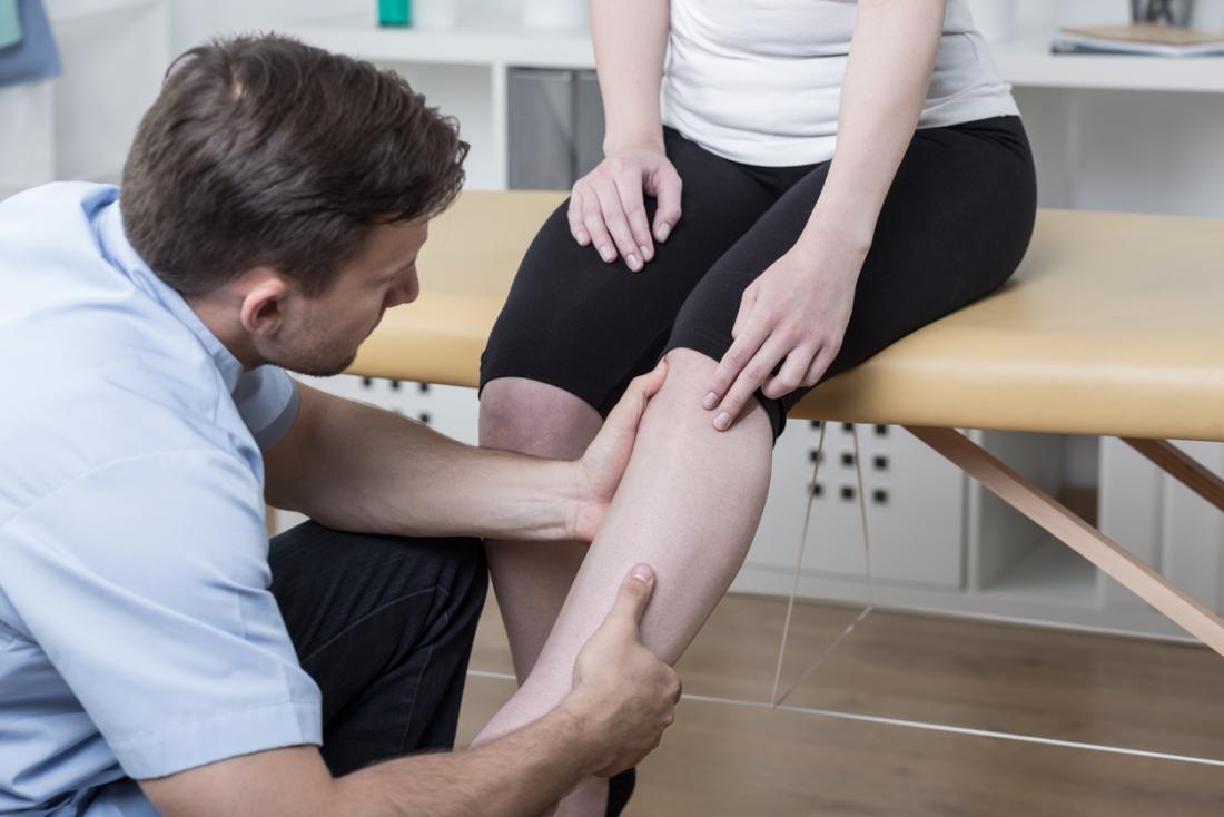 Chiropraktor, der Knie und Bein des Patienten betrachtet, während sie auf Bett sitzen.