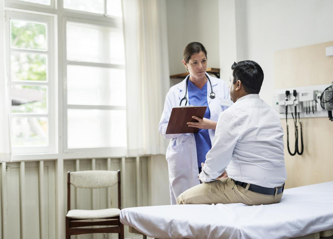 Doktor, der mit männlichem Patienten auf Bett spricht