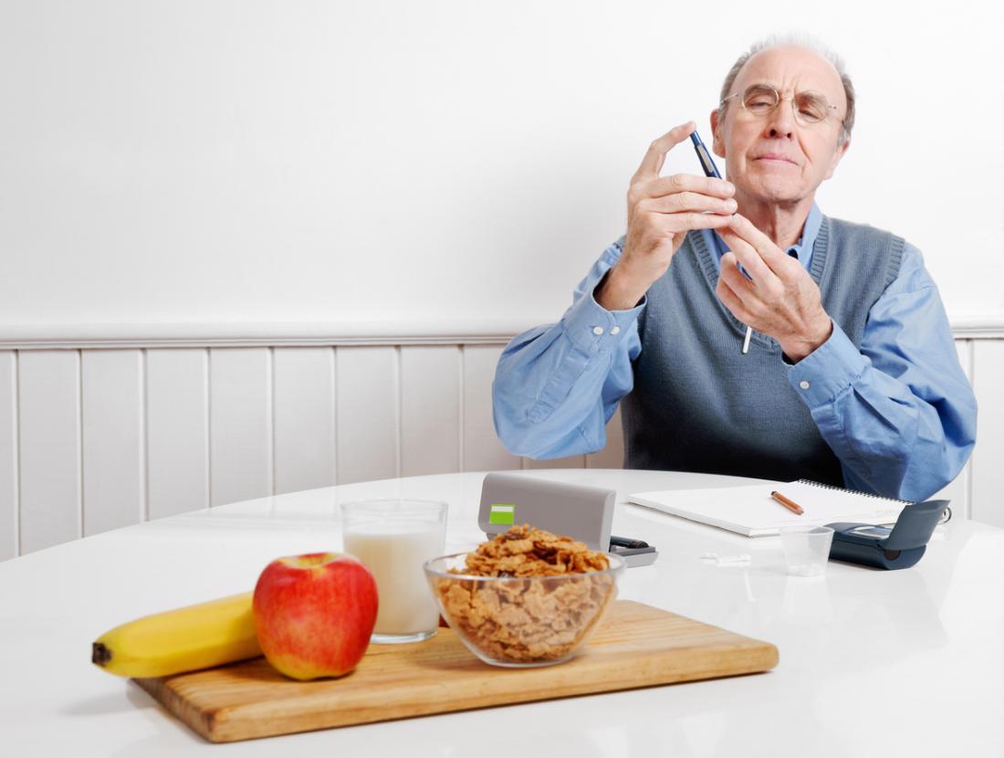 người đàn ông kiểm tra lượng đường trong máu trước khi ăn sáng