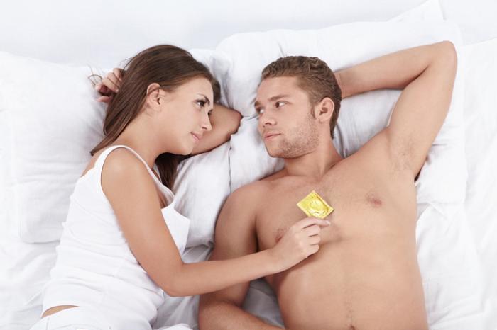 Mann und Frau im Bett, das ein Kondom hält
