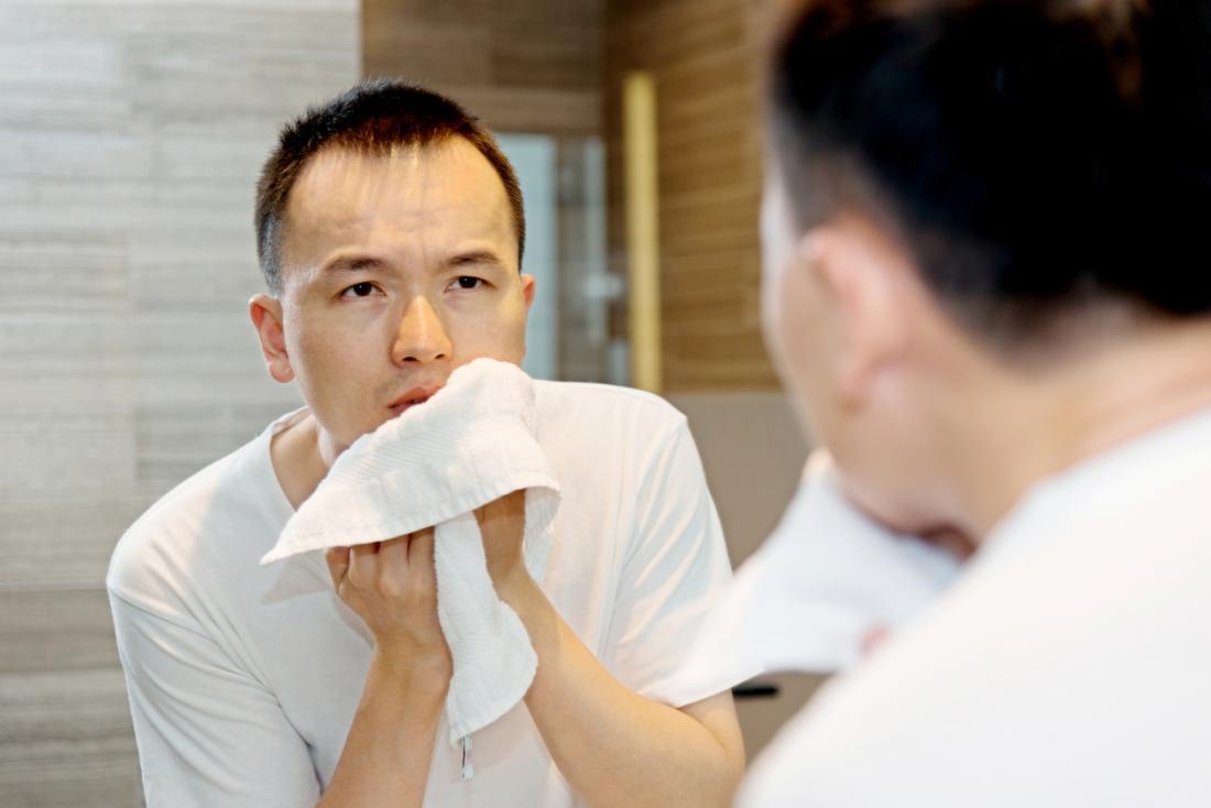 Homem asiático novo que lava e que seca sua cara com a toalha para se livrar da fervura.