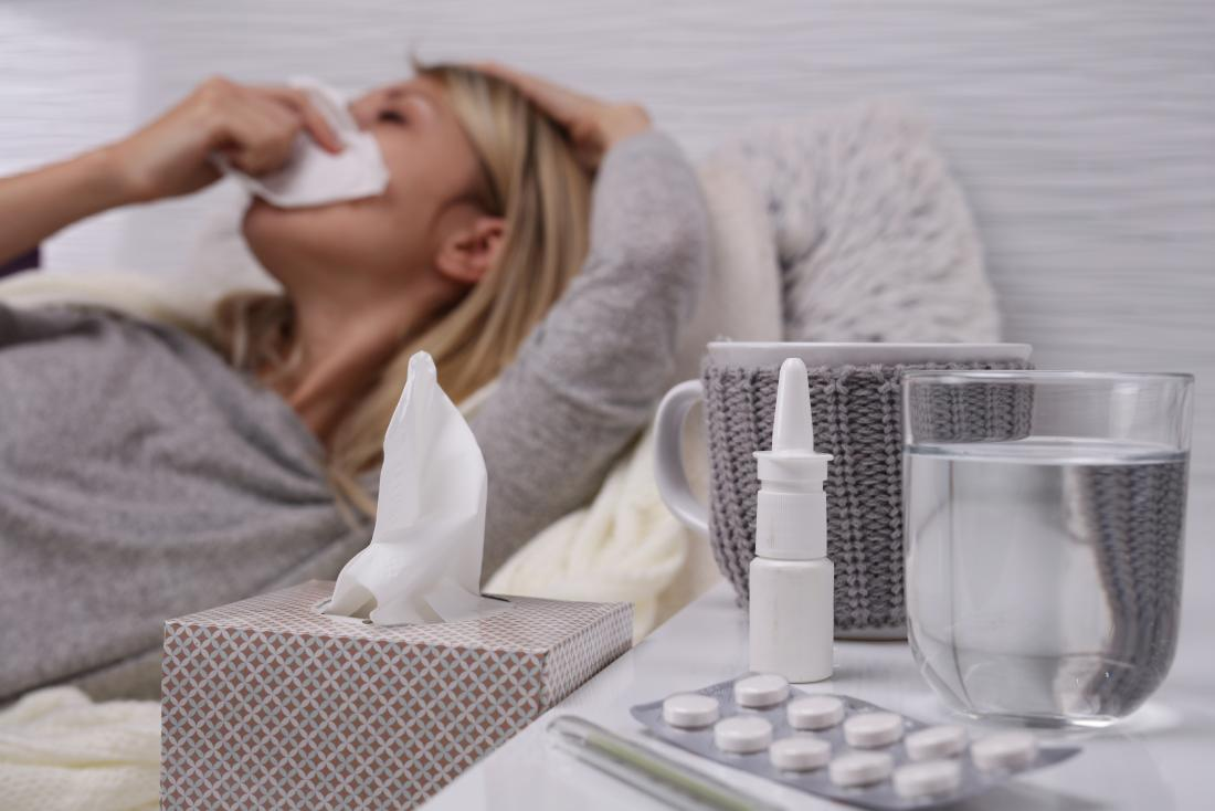 寒さやインフルエンザに苦しんでいる女性は、組織、水、鼻スプレー、投薬を使って痰や粘液を取り除いています。
