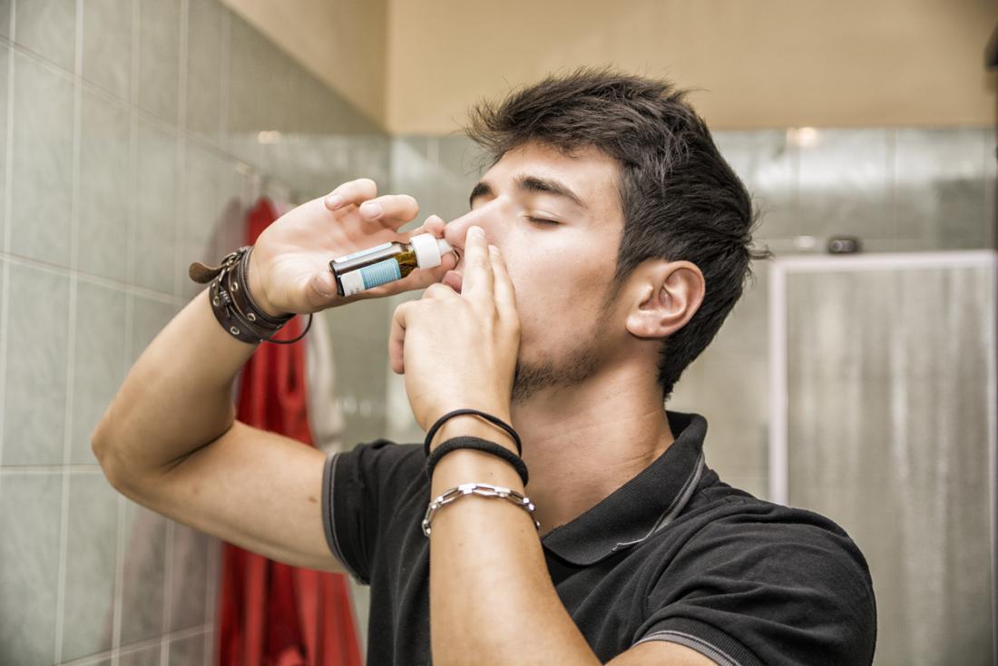 バスルームで鼻スプレーを使用している男。