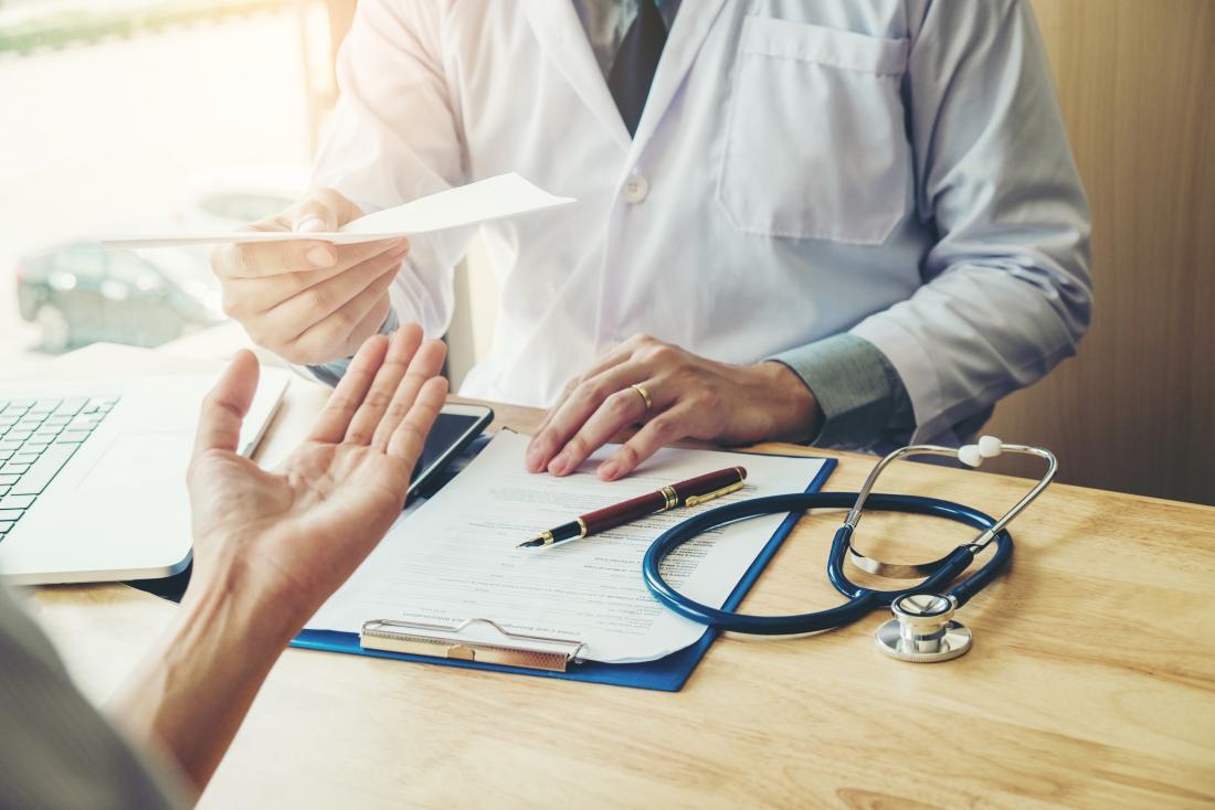 医者は患者に机の上で処方箋を渡す。