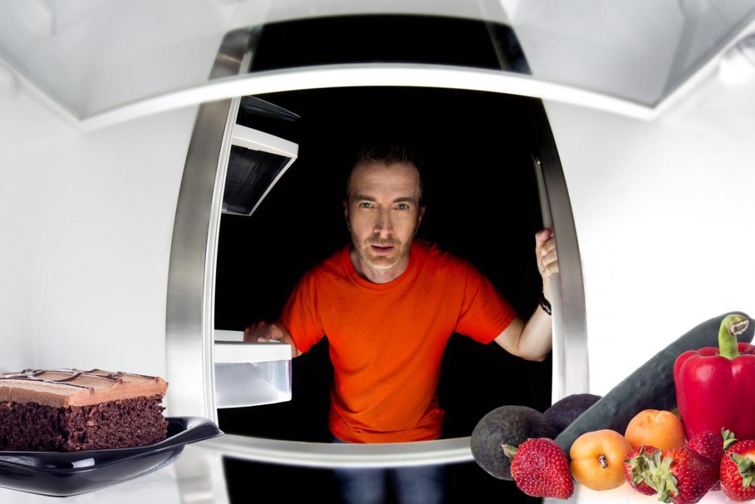 homme regardant dans un réfrigérateur