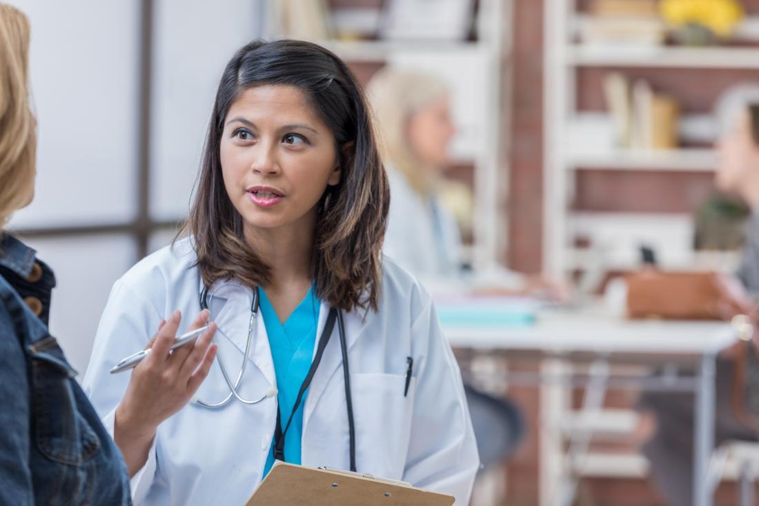 Ärztin, die mit Patienten im offenen Büro spricht.