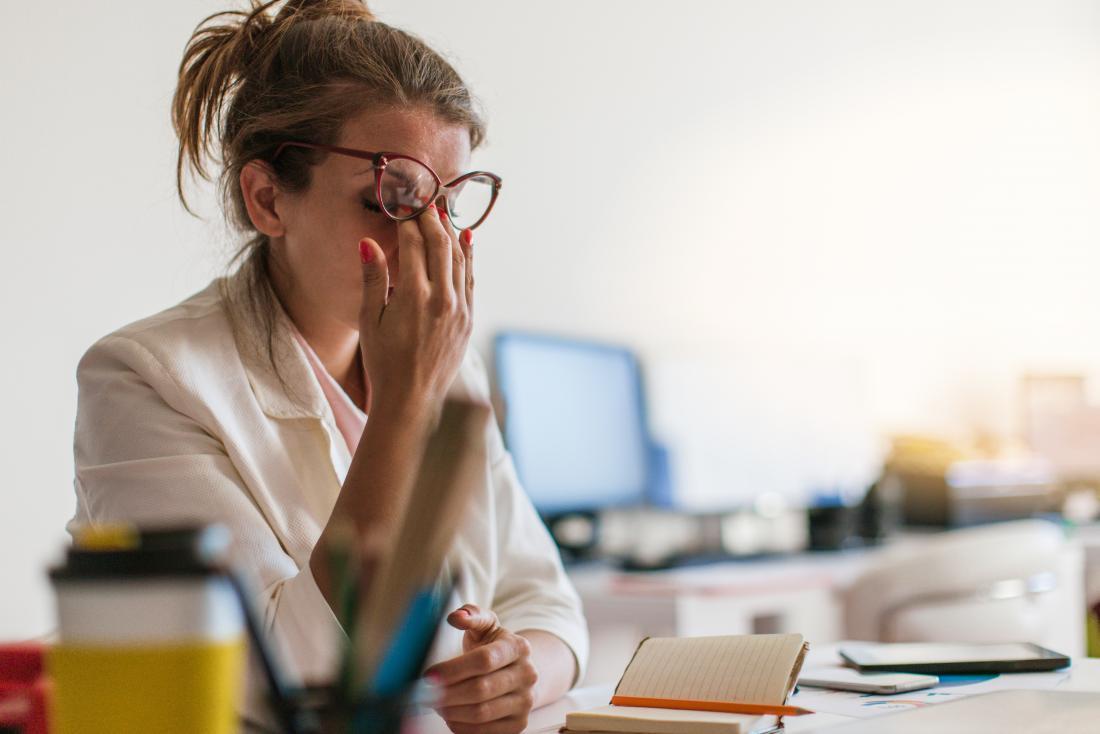 Zestresowana i zmęczona kobieta ociera oczy w pracy.