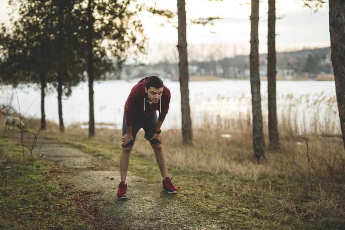 Giovane in attrezzatura da jogging, senza fiato dopo aver eseguito nei boschi dal lato di un lago.