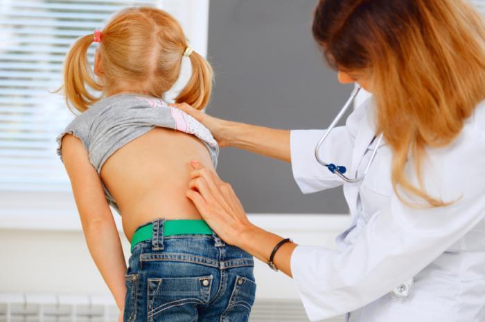 [médico olha para as costas da criança]