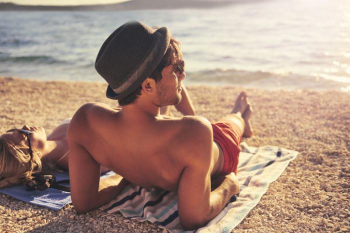 男はビーチで日光浴