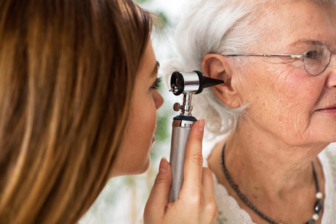 Възрастна жена, която има ухо, инспектирано от лекар.