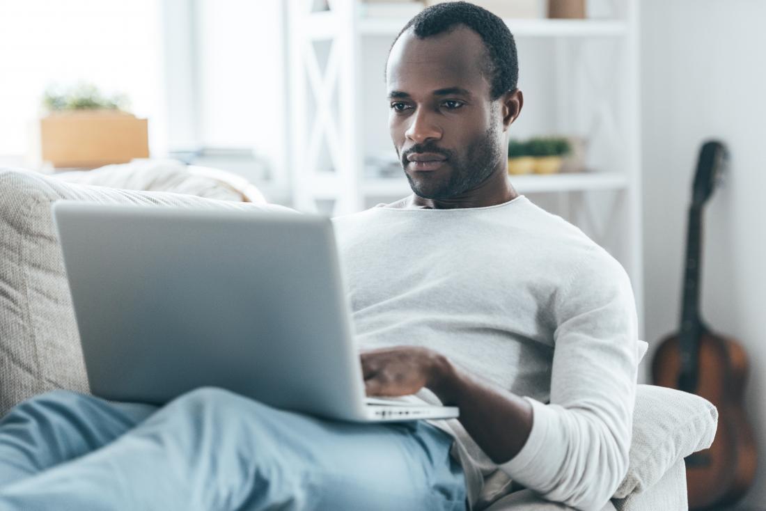 Uomo a casa sul divano, guardando online con il portatile.