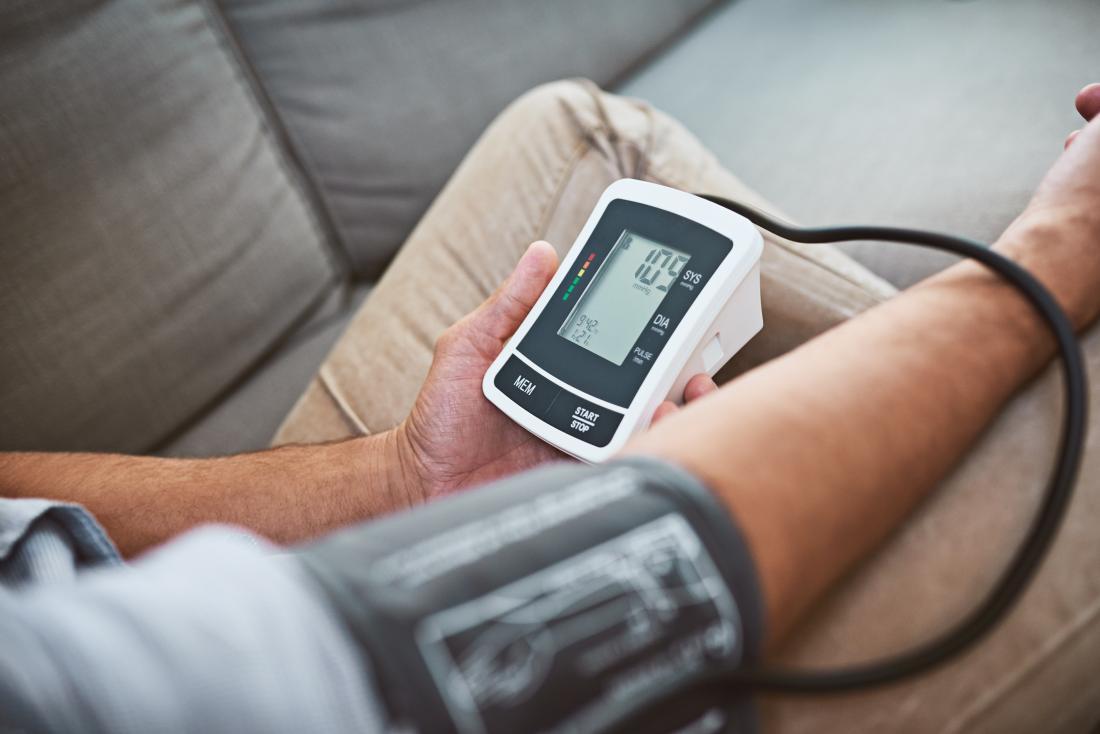 Uomo che misura la sua pressione sanguigna con banda e monitor