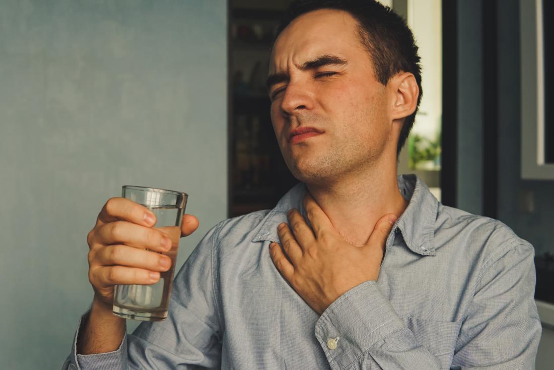 Mn avec la gorge sèche se serrant le cou de douleur, et tenant un verre d'eau.