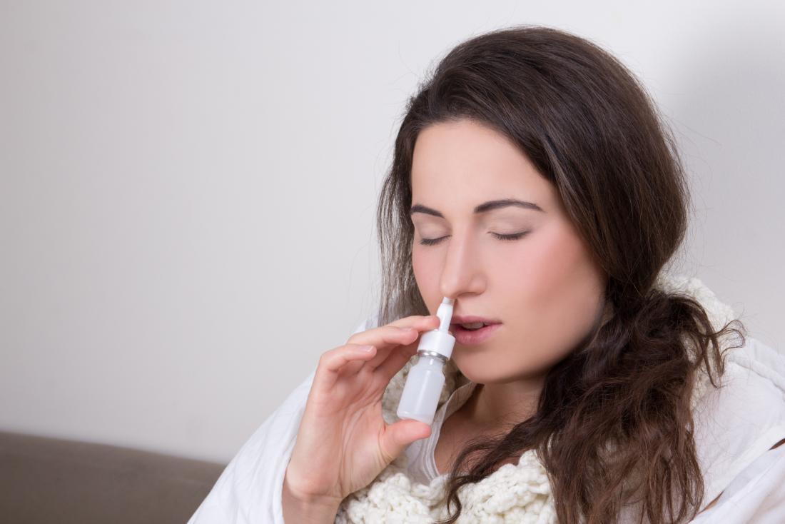 Femme utilisant un spray nasal décongestionnant.