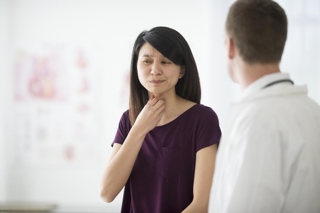 医者の手術で喉の痛い女性