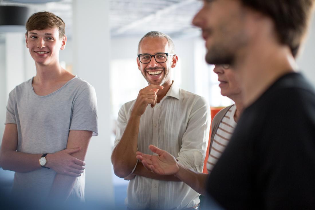 Grupo de colegas de trabalho em um grupo sorrindo e rindo.