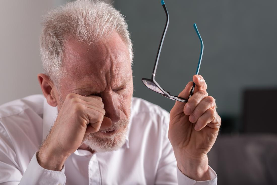Un homme âgé fatigué avec des yeux qui piquent et qui se frottent les yeux avec des lunettes.