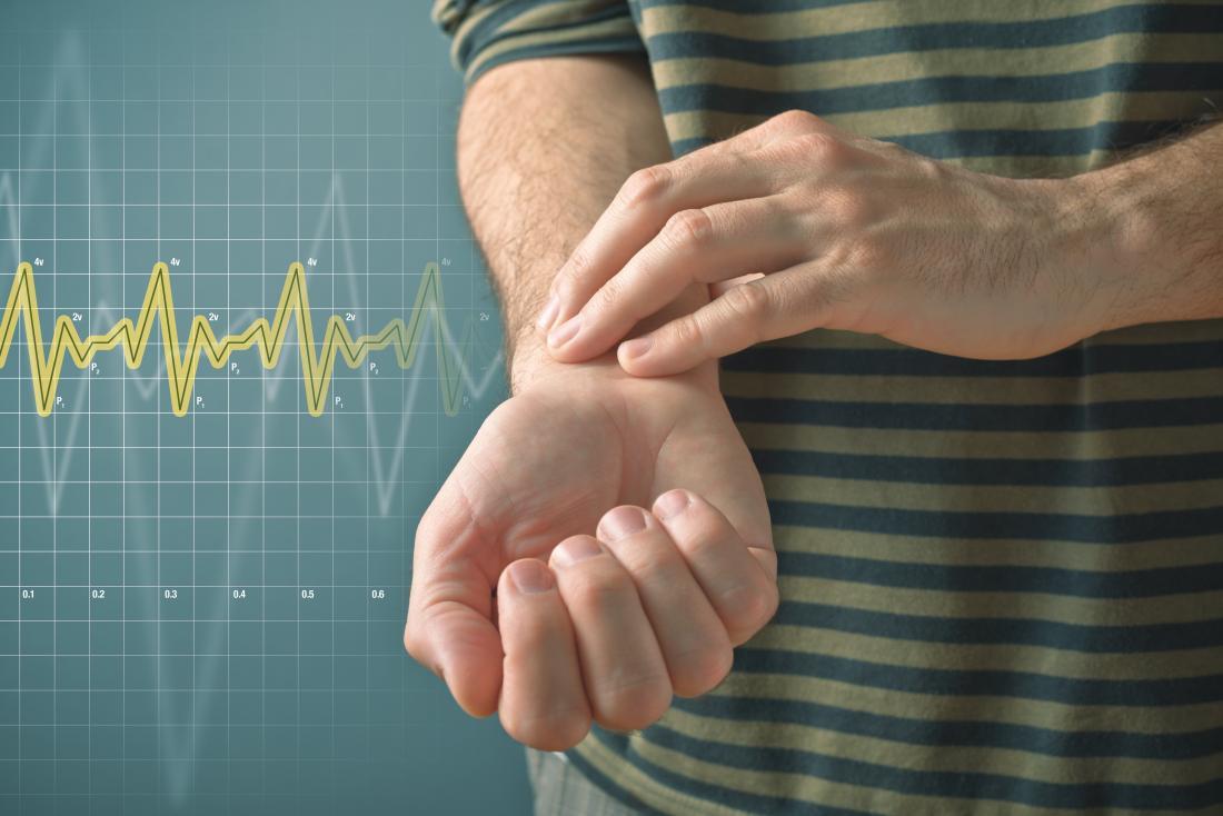 Човек понижава сърдечната честота с пръсти на китката, за да измерва пулса.