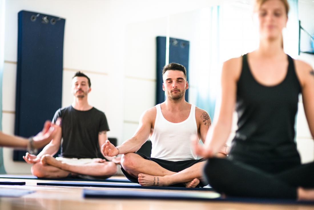 Йога клас в медитация представляват, с човек в средата на йога mat.
