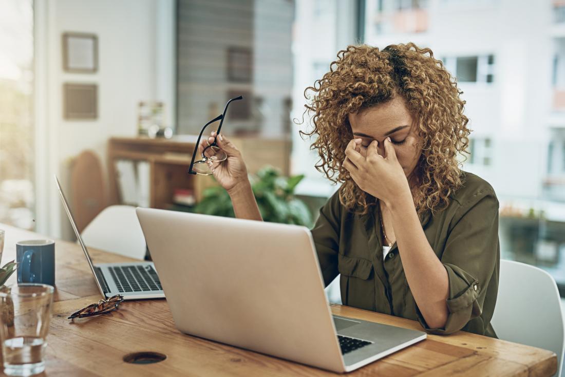 Стреснати жени, работещи в домашен офис, с два лаптопа, които търкат мост от носа поради напрежение главоболие.