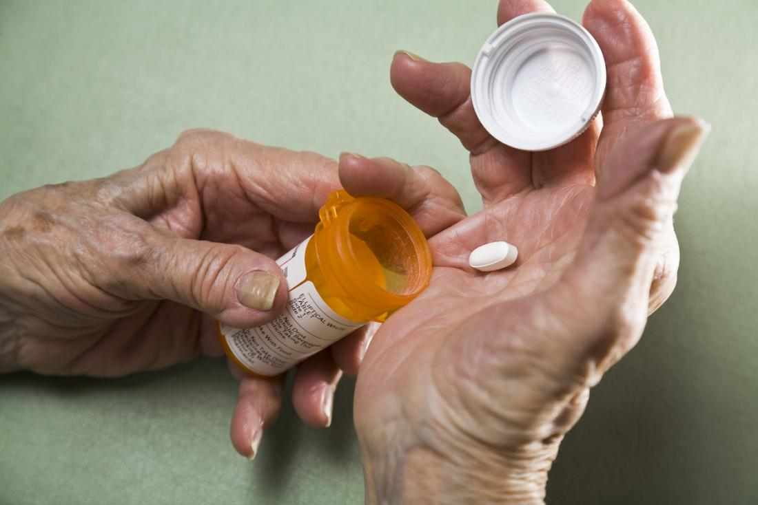 Pessoa com artrite, com pílula de medicina na palma da panela de drogas de prescrição.