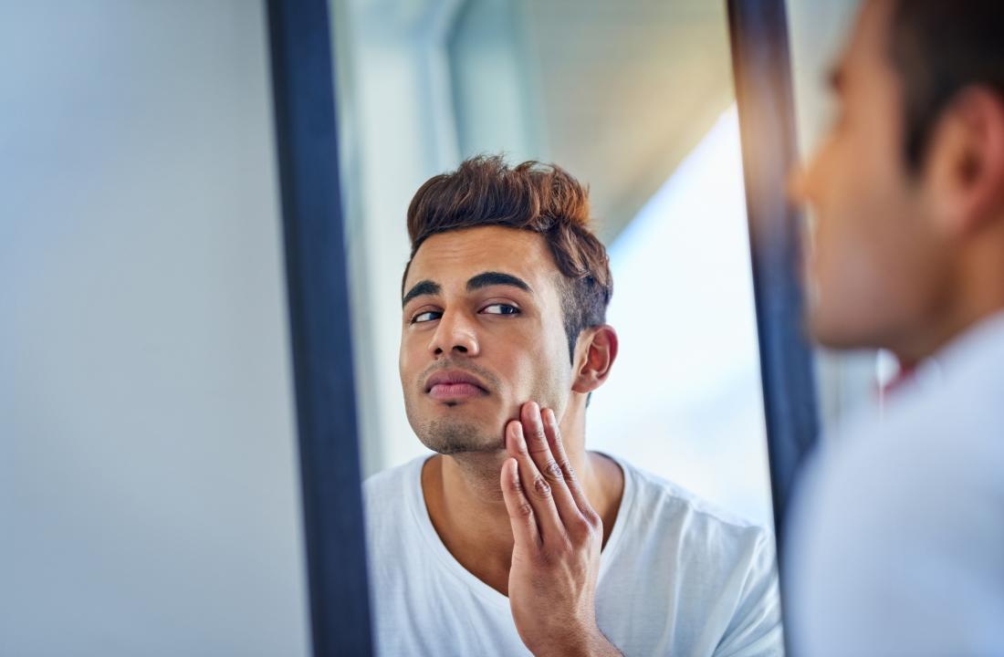 鏡の中を見ている傷病を予防したい男