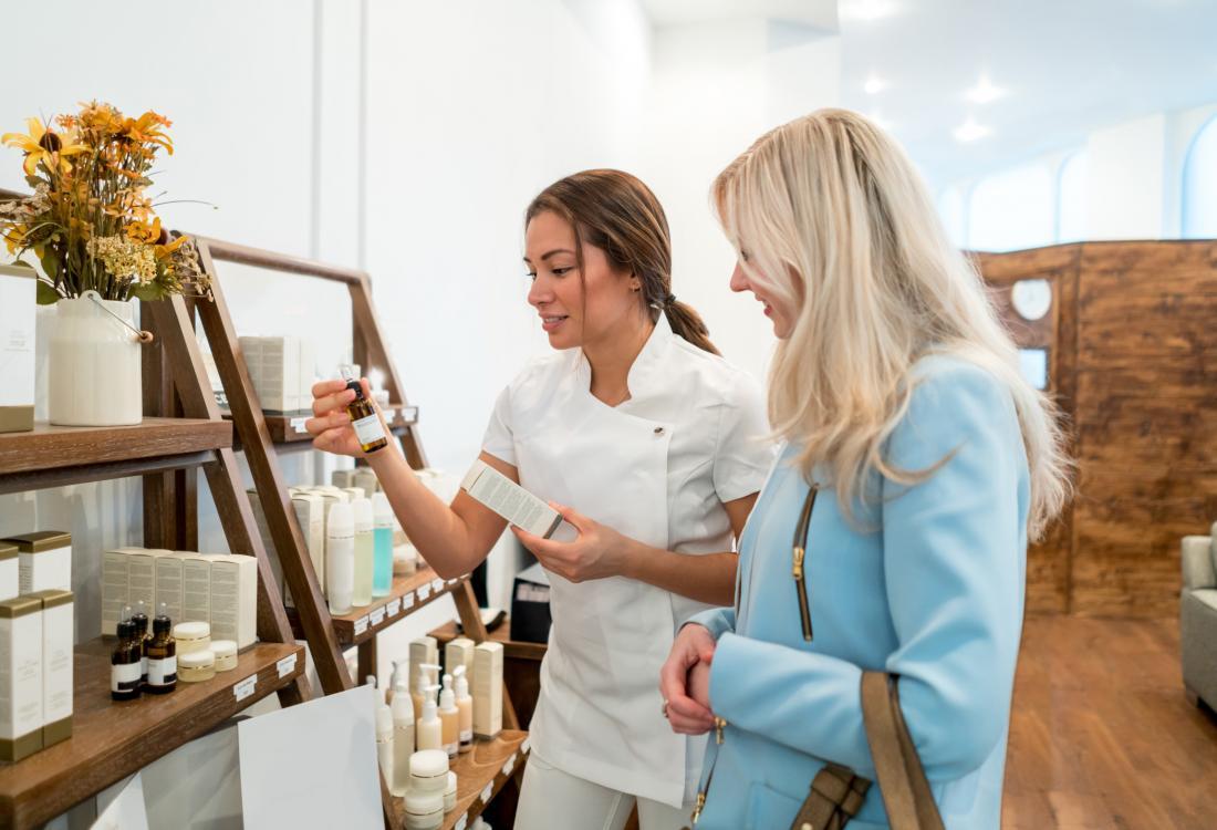 スパ・ワーカーからの助けを受けているスキンケア製品を買い取っている女性。