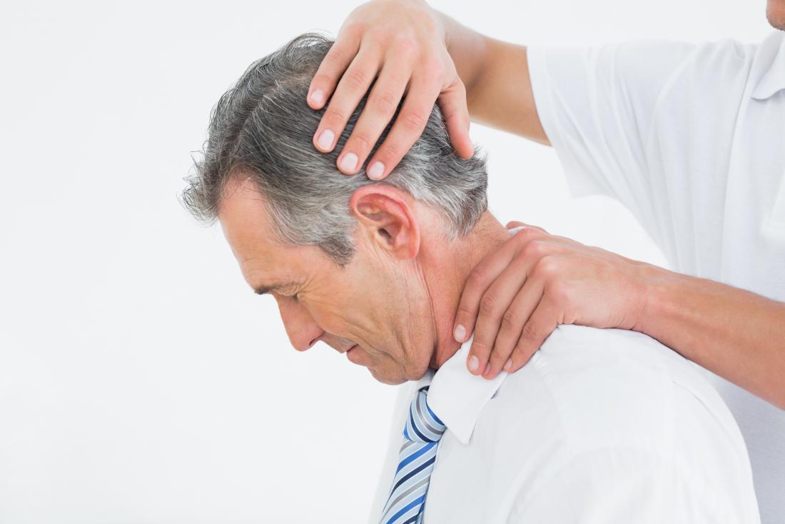 Uomo con collo manipolato dal chiropratico durante la terapia fisica.